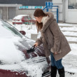 Woman cleaning her car after snow blizzard — Stock Photo