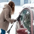 Woman with long hair cleaning car after blizzard — Stock Photo