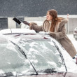 Young woman cleaning snow from car roof using brush — Stock Photo
