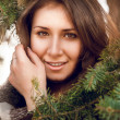 Portrait of young woman in plaid behind fir tree — Stock Photo