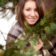 Portrait of woman in plaid behind fir tree — Stock Photo #40488305