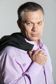 Portrait of mature man holding his jacket over shoulder — Stock Photo