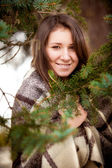 Portrait of woman in plaid behind fir tree — Stock Photo