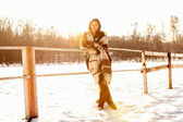 Portrait of woman leaning at fence on ranch at winter day — Stock Photo