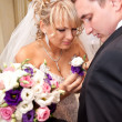 Stock Photo: Blonde bride adjusting boutonniere on groom jacket