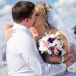 Newly married couple kissing against blue sky — Stok fotoğraf