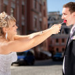 Greedy bride taking lollipop from groom while he was eating it — Stock Photo #40639477