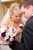 Blonde bride adjusting boutonniere on groom jacket — Stock Photo