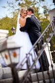 Mooie bruid bruidegom kijken en hand in hand op zijn schouder — Stockfoto