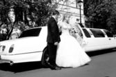 Black and white photo of bride and groom standing near limousine — Stock fotografie