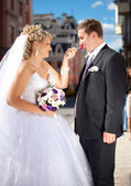 Funny portrait of bride giving lollipop to groom — Стоковое фото