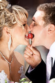 Portrait of newly married couple eating on lollipop — Stock Photo