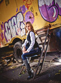 Blonde woman sitting on stairs against cabin with graffiti — Stock Photo
