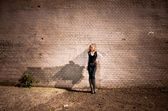 Blonde woman leaning against long tiled wall on street — Stok fotoğraf