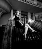 Sexy woman in dress sitting on big industrial bobbin — Stock fotografie