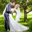 Stock Photo: Groom bending over bride and kissing her passionately at park