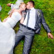 Newly married couple lying on grass and kissing — Stock Photo