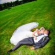 Newly married couple lying on grass at park — Stock Photo #41103677