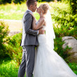 Handsome groom kissing blonde bride at park on lawn — 图库照片 #41103859