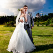 Bride and groom standing on grass and looking at sky — Stock Photo