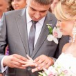 Young handsome groom putting wedding ring on brides finger — Stock Photo