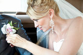 Blond bride attaching boutonniere on husbands jacket — Stock Photo
