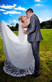 Portrait of bride with long veil kissing groom in suit — Stock Photo