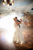 Bride and groom dancing in smoke — Stock Photo