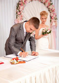 Portrait of young groom signing wedding contract — Stock Photo
