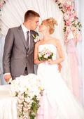 已婚夫妇装饰弓下的接吻第一次 — 图库照片