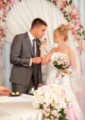 Young bride giving chocolate candy to groom — Stockfoto
