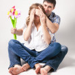 Man closing eyes of pregnant wife and giving her flower — Stock Photo