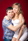 Portrait of husband hugging pregnant wife seated on legs — Stock Photo