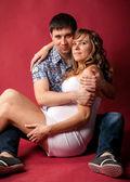 беременная женщина, лежа с мужем на красном фоне — Стоковое фото