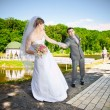 Outdoor portrait of bride pulling by hand resist groom — Stock Photo #41614395
