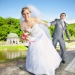 Bride pulling handsome groom by hand at park — Stock Photo #41614411