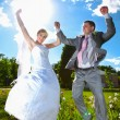 Married couple holding hands and jumping high at the park — Stock Photo