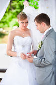 Groom putting wedding ring on brides hand at alcove — Stock Photo