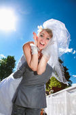 Man in suit kidnapping screaming bride — Stock Photo