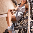 Woman in dress and high heels sitting on metal stairs — Stock Photo