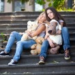 Teenage girls sitting on stairs outdoor and holding teddy bears — Stock Photo