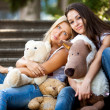 Portrait of two beautiful girls sitting on stairs with teddy bears — Stock Photo #41646829