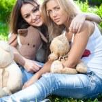 Beautiful teenage girls sitting on grass with teddy bears — Stock Photo