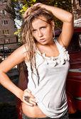 Portrait of wet blonde woman in white singlet on street — Stock Photo