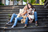 Teenage girls sitting on stairs outdoor and holding teddy bears — ストック写真