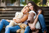 Portrait of two beautiful girls sitting on stairs with teddy bears — Stock Photo
