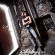 Slim girl posing at porch in old abandoned building — Stock Photo #41818945