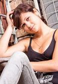 Portrait of sitting sexy brunette girl in black singlet — Stock Photo