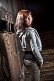 Teenage girl standing on stairs at old abandoned building — Stock fotografie