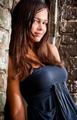 Brunette girl with big breast leaning against brick wall — Stock Photo